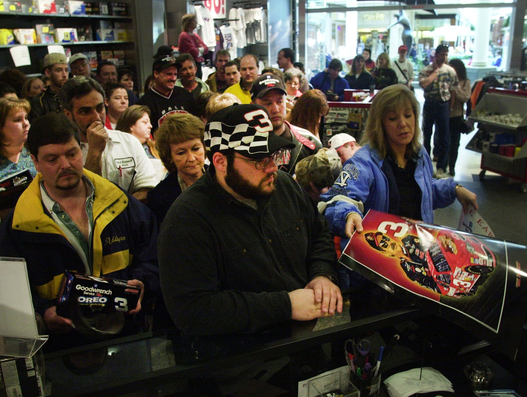 "Stephen Sheriff, center, and Julie Ray, right, were among the throng of fans buying Dale Earnhardt memorabilia the day after his death on Monday, Feb. 19, 2001, at the NASCAR Thunder store in West Town Mall. ""It was the day that NASCAR died. It's like those lines from the Don McLean song---'February made me shiver' and ""Drove my Chevy to the levee,"" "" said Ray, a North Carolina native now living in Knoxville. (Paul Efird/ News-Sentinel)"