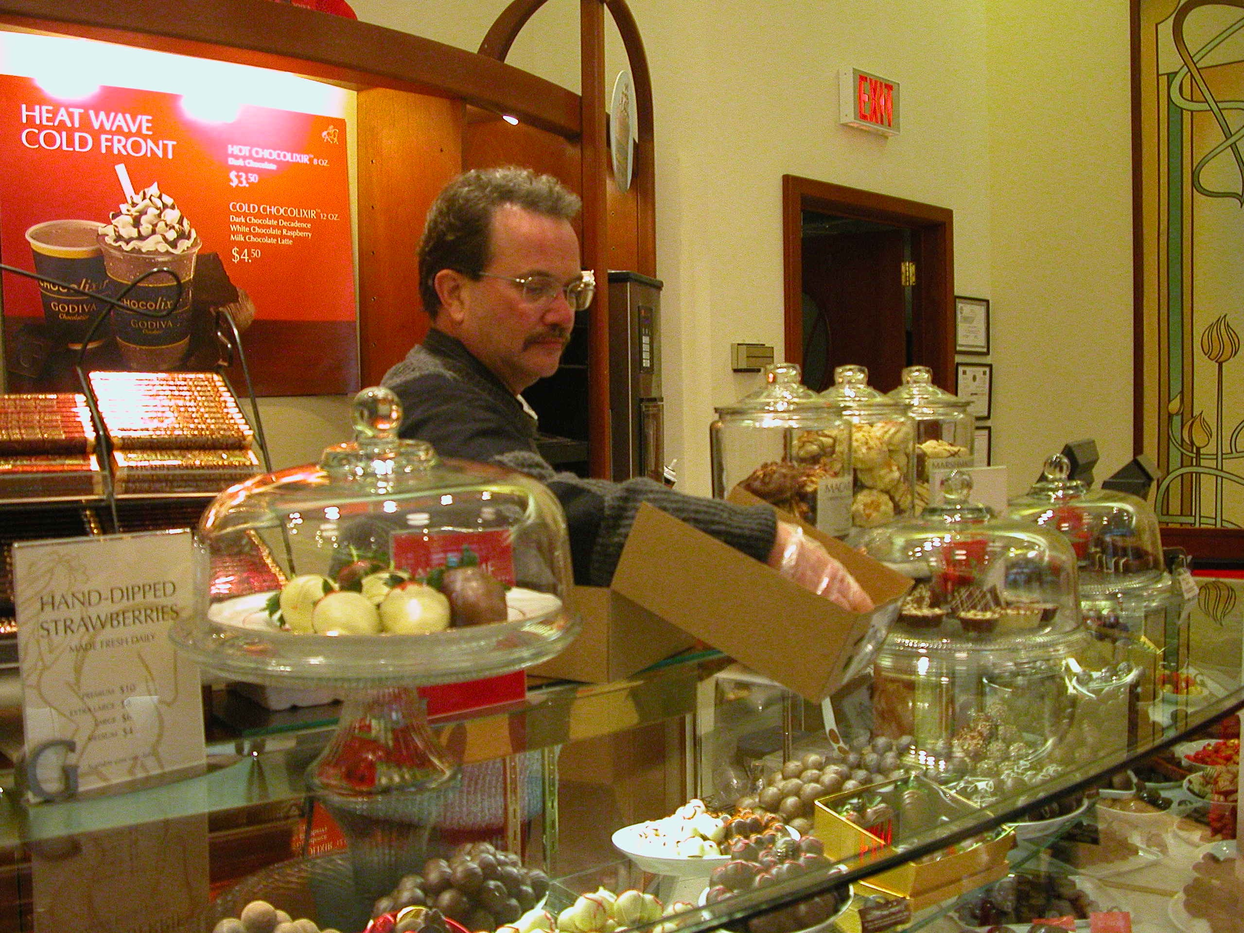 Stan Latham, manager of Godiva Chocolates, prepares gift boxes at West Town Mall.
