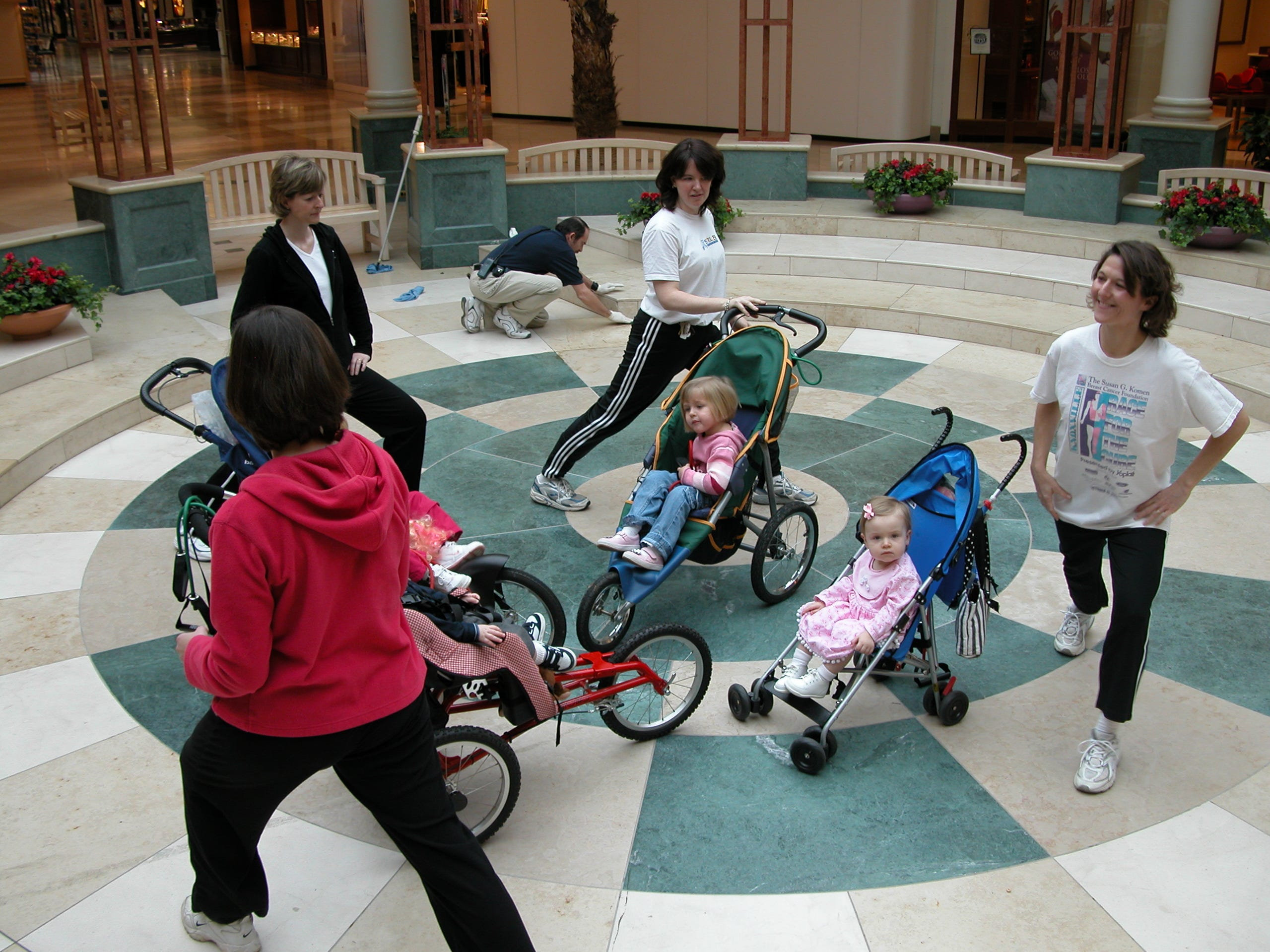 Participating in the new Stroller Strides fitness class for moms and infants or toddlers at West Town Mall are, from left, moms Helen Arnold (in red jacket), of Sequoyah Hills, Elizabeth Gregor of Lyons Crossing, leader Caroline Mann of Westwood, and Amy Weller of Lovell Heights. In the strollers are, 3-year old Devon Kay Weller and 16-month-old Sophie Gregor. Obscured by the exercisers are 16-month old Robert Mann and 3-year old Alice Arnold.