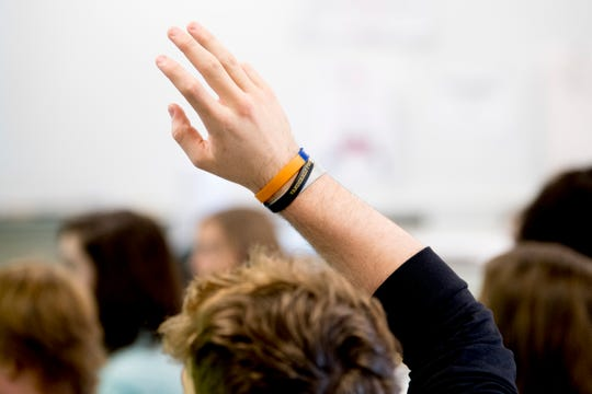 A student raises a hand for a question in Anita Crook's medical therapeutics class at Maryville High School.