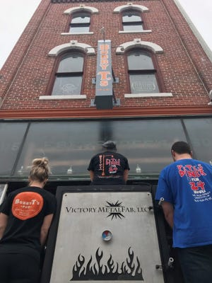 Employees of Bobby T's stand outside the pub with owner Robert Turner's new smoker. From left to right pictured- Brittany Herriot, Alyssa Rowe and Andrew Corcoran.