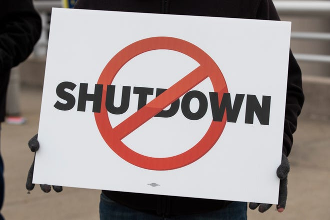 Federal Aviation Administration employees hold signs in protest of the government shutdown at Louisville International Airport on Tuesday,  Jan. 15, 2019.