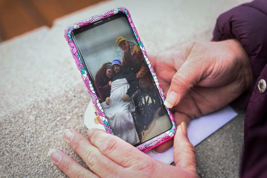 Brandy Stafford shows a photo of herself with her father Tim Ramey, right, and her brother James Ramey from when James was in the hospital in Inez, Ky. on Jan. 8, 2019. They lost James to complications due to Hepatitis A in November 2018.