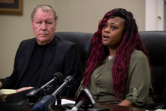 Attorney T.J. Smith, left, sits with his client, Kianna Miller, the mother of two boys injured in a hit-and-run on Halloween. Miller has filed a lawsuit against JCPS for their handling of busing issues that she and her lawyers believe led to the incident.