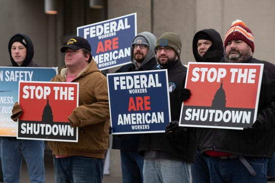 Federal Aviation Administration employees hold signs in protest of the government shutdown at the Louisville International Airport on Jan. 15.