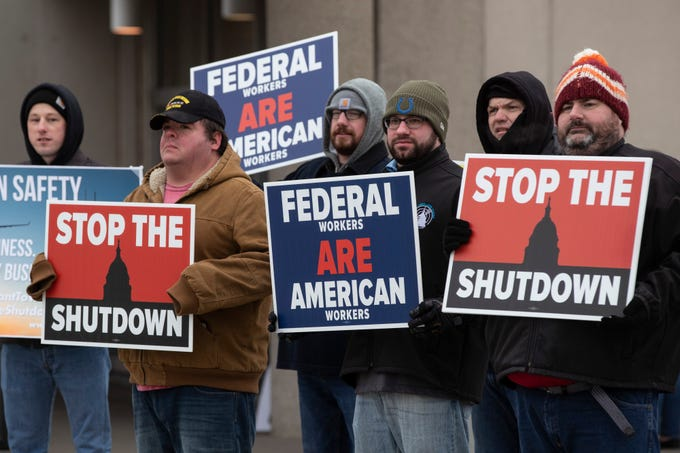 Federal Aviation Administration employees hold signs in protest of the government shutdown at the Louisville International Airport on Tuesday. Jan. 15, 2019