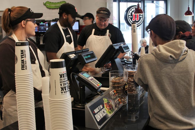 Brittney Greenawalt stands behind the counter at Jimmy John's during her official first day of work on Tuesday. The sandwich shop opened its doors to the public for the first time earlier that morning on Marion-Mount Gilead Road.
