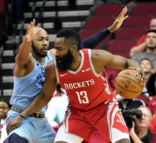 Memphis Grizzlies' Jevon Carter, left, defends against Houston Rockets' James Harden (13) during the first half of an NBA basketball game Monday, Jan. 14, 2019, in Houston.(AP Photo/David J. Phillip)