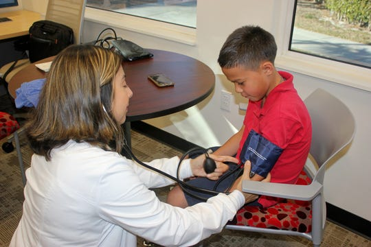 Core Healthy Partners' Nurse Navigator, Monica Ramos, checks Jon's blood pressure at the Marco YMCA.