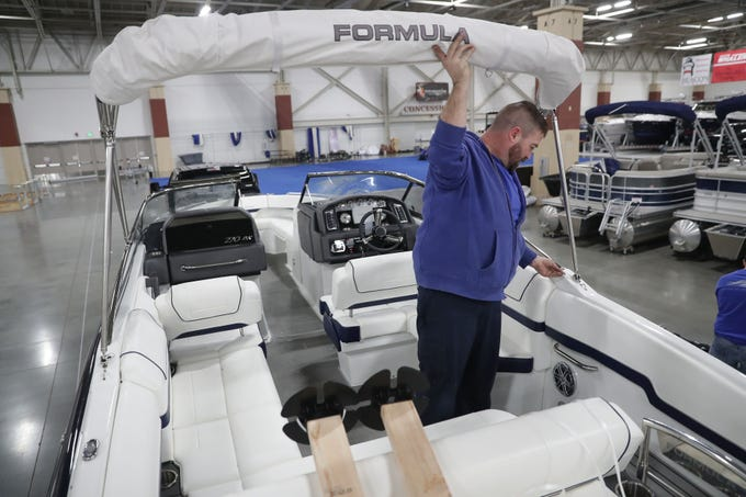 Adam Thomas, with Shipyard Marina in Green Bay, sets up a Formula 270 bow rider speed boat. Preparations were underway for the Milwaukee Boat Show at State Fair Park in West Allis on Tuesday. The show runs Friday through Sunday, and again Wednesday though Jan. 27.