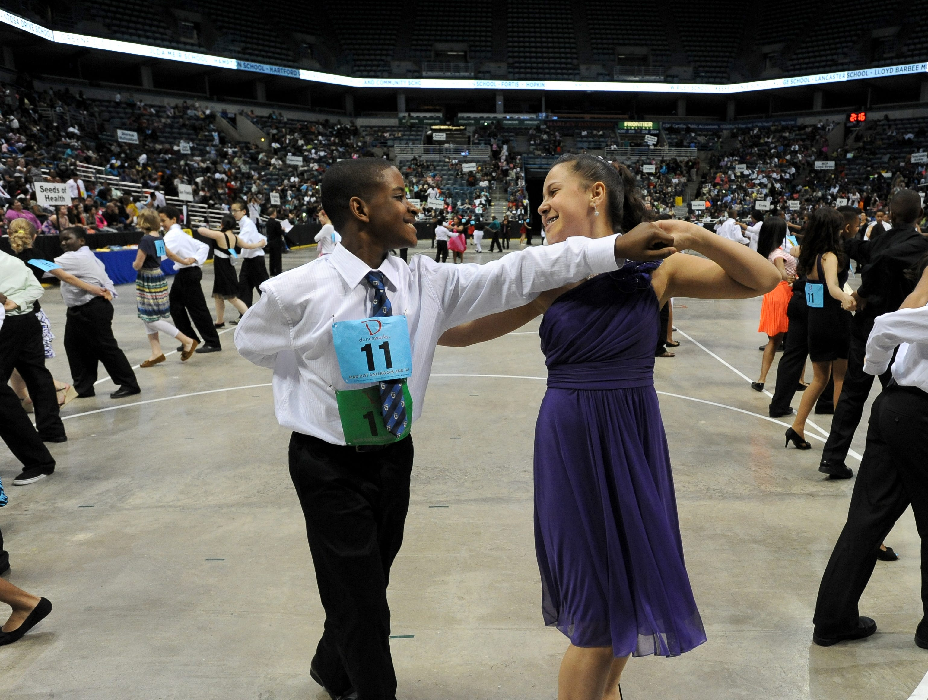 2013: Myles Walker, left, and partner Pele Salinas, right dance the cha cha. Nearly 2,200 local students from 43 area schools perform and compete in the Mad Hot Ballroom show at the Bradley Center.