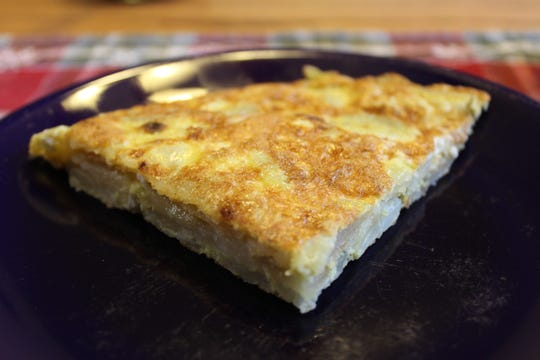 The Spanish potato omelet is cut into wedges to serve.