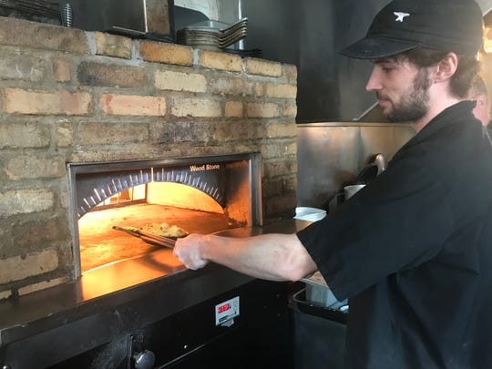 Chef Brad Connell takes one of Anvil's pasta dishes out of its wood stone oven.