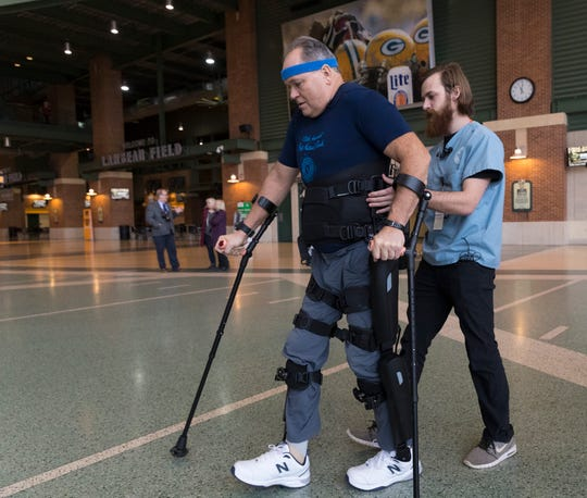 Dean Juntunen is aided by VA physical therapist Zach Hodgson while walking with the use of a robotic exoskeleton inside the atrium at Lambeau Field in Green Bay. The Milwaukee VA is studying the use of exoskeletons that allow some people with paralysis to walk.
