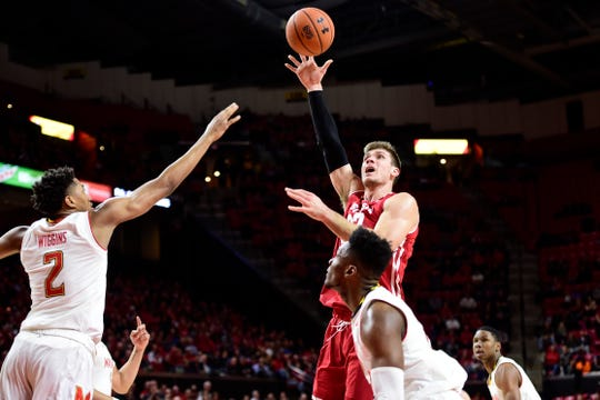 Jan 14, 2019; College Park, MD, USA;  Wisconsin Badgers forward Ethan Happ (22) shoots as Maryland Terrapins guard Aaron Wiggins (2) and  forward Bruno Fernando (23) defends in the first half at XFINITY Center. Mandatory Credit: Tommy Gilligan-USA TODAY Sports