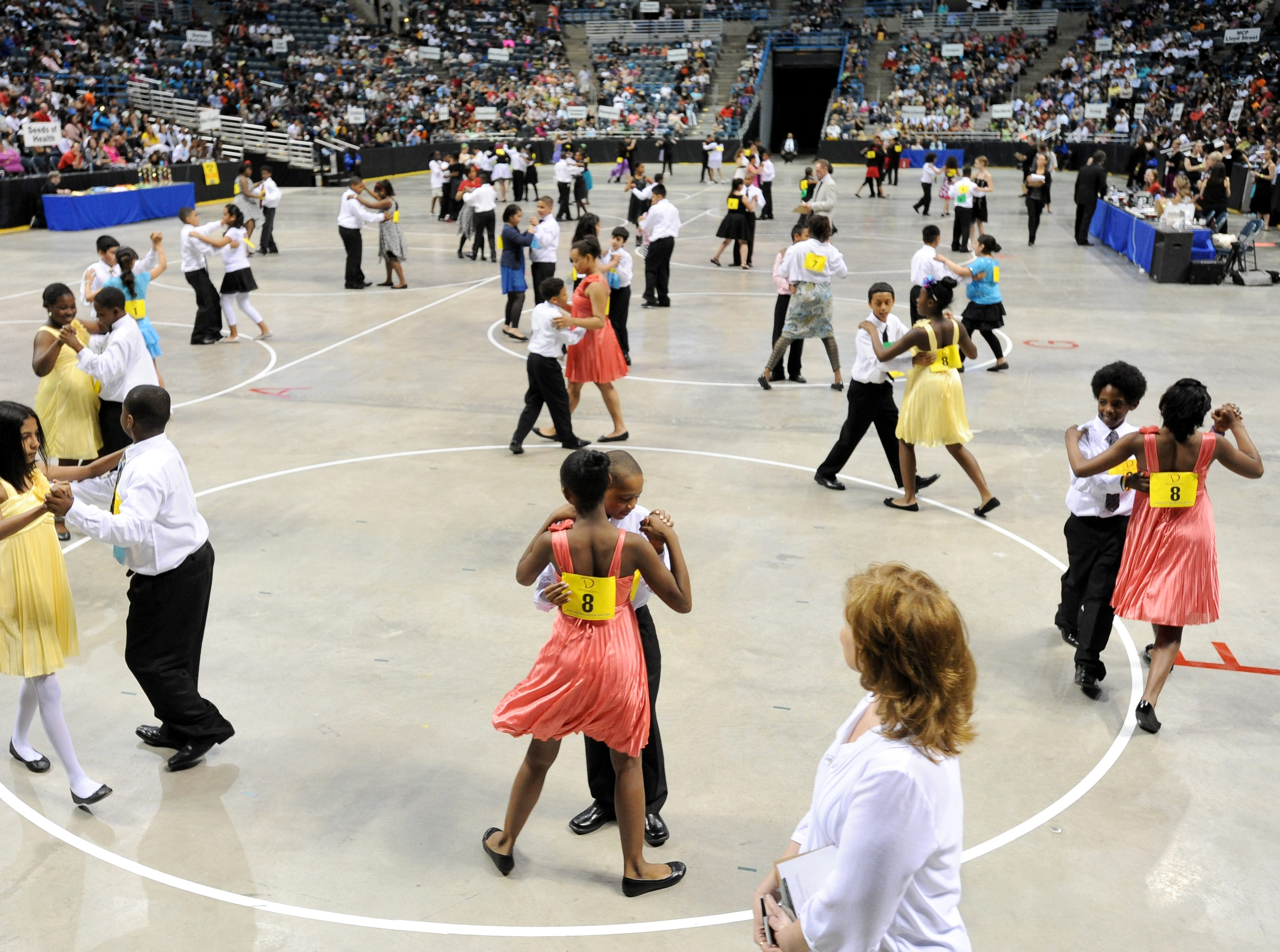 2013: A judge looks out onto a group of students as they perform the fox trot. Nearly 2,200 local students from 43 area schools perform and compete in the Mad Hot Ballroom show at the Bradley Center.