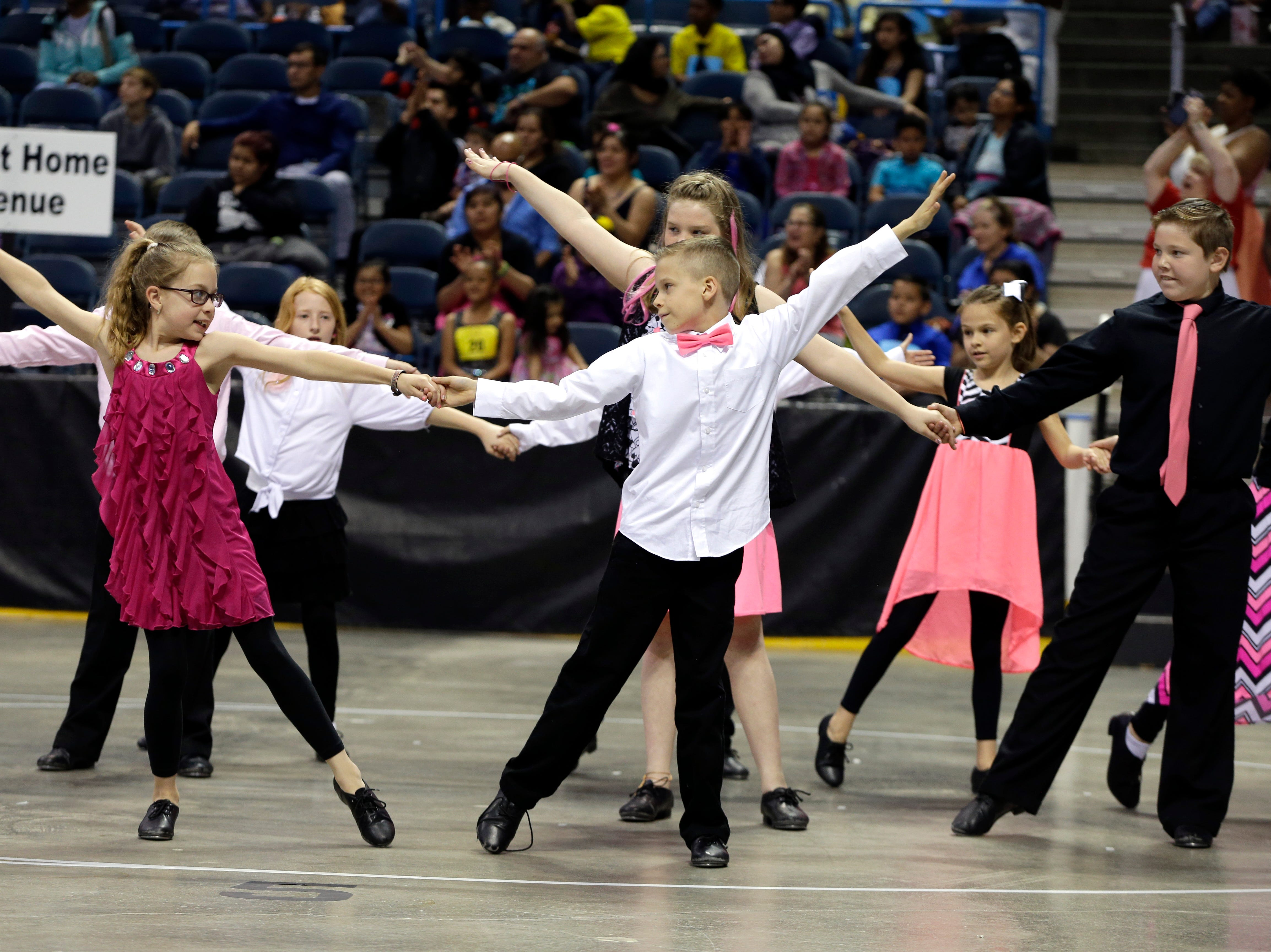 2016: Joelle Smith, 10, left and Lincoln Vegin, 10 middle, perform with other Elm Dale school students in the annual Mad Hot Ballroom and Tap competition at the BMO Harris Bradley Center.
