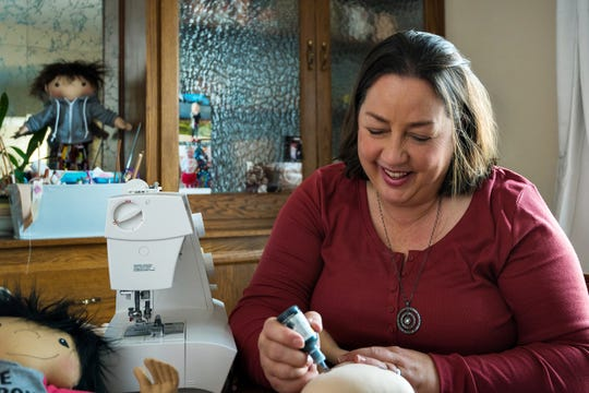 "Amy Jandrisevits works on one of her Doll Like Me creations at her New Berlin home. The dolls are made for girls who are somehow ""different,"" often a physical deformity. Jandrisevits custom designs to doll to look like the intended recipient."