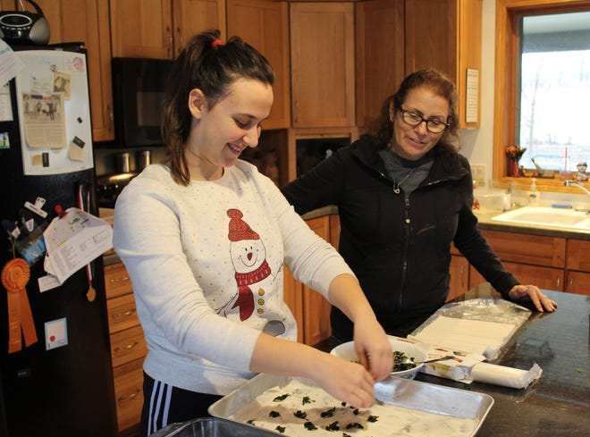 Bora Ajdini talks with her host mom, Ann Weeden, while fixing her potluck recipe.