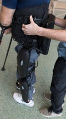 Dean Juntunen is aided by VA physical therapist Zach Hodgson while walking with the use of a robotic exoskeleton.