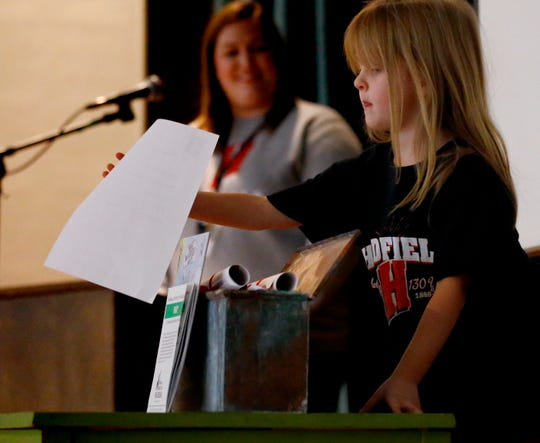 Makenzie Ziller places an item to be added to Hadfield Elementary School's time capsule to be returned to the building's 1950 cornerstone during an all-school assembly on Jan. 15 as part of the school's 131st anniversary celebration. The original Hadfield School opened on Jan. 15, 1888, and the current building was constructed on the property in 1950.