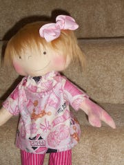 Amy Jandrisevits made this doll for a girl named Hope Kiszka, a young teenage girl who was born with two fingers on her left hand and a birthmark on that arm. The girl was overcome with emotion when she first saw her Doll Like Me gift, which was made to resemble her.