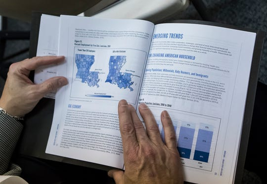 An audience member of the 2018 A.L.I.C.E. report flips through the report booklet at the United Way of Northeast Louisiana's office in Monroe, La. on Jan 15. The report details the financial instability of working families in La.