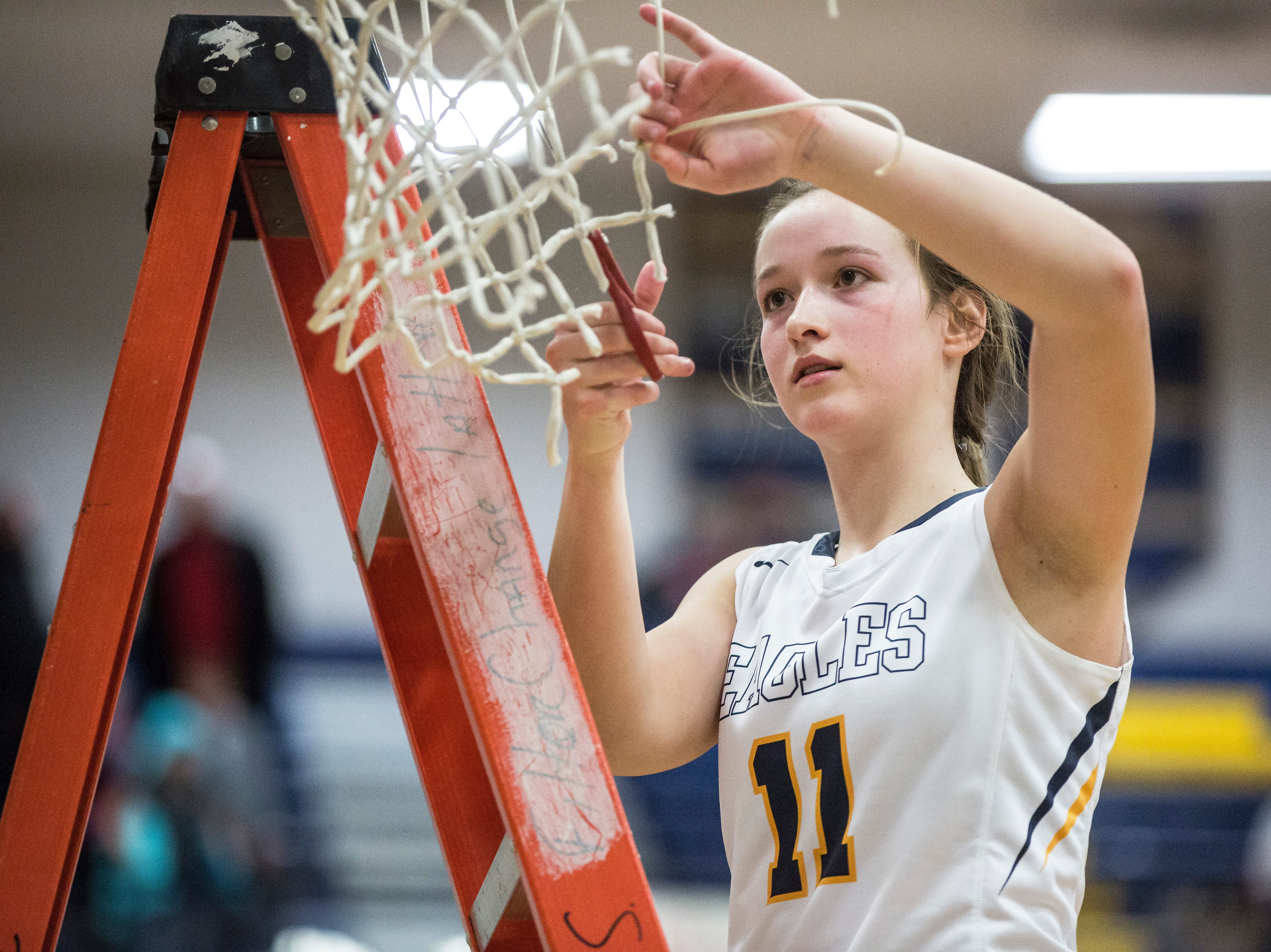 Delta's Kassidy Dishman cuts down the net Monday evening after winning the Delaware County Basketball Tournament championship game at Delta High School. Delta won the game 42-32.