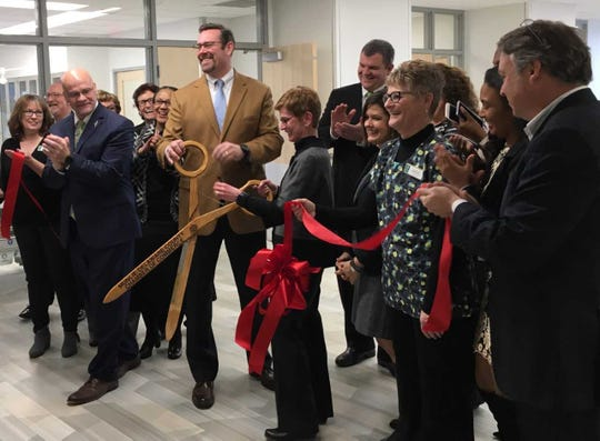 Jud Fisher cuts the ribbon to open the schools of nursing and health sciences at Ivy Tech Community College in Muncie on Tuesday.