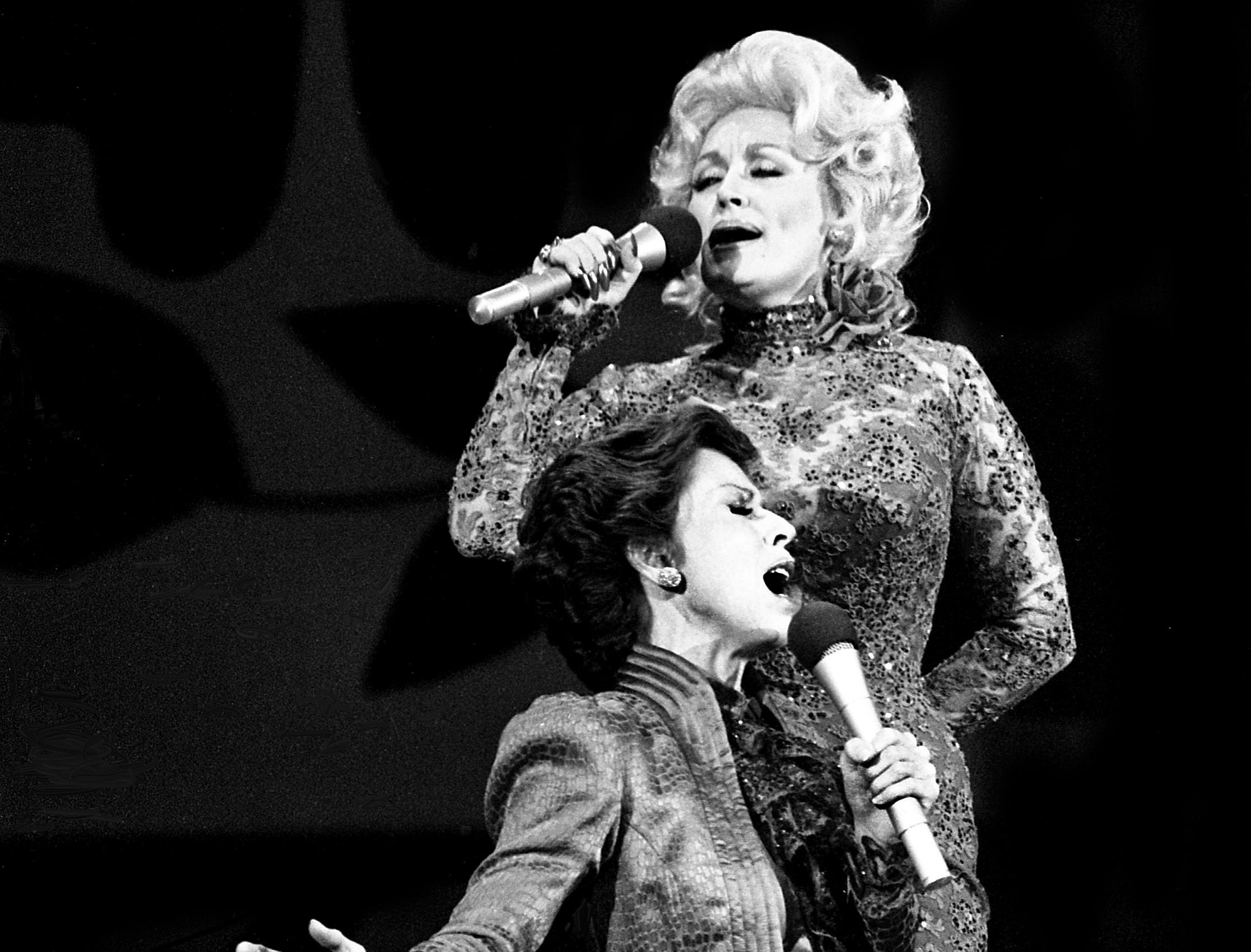 """Carol Burnett and Dolly Parton are performing during their mock-melodramatic love song skit during the taping of the """"Dolly and Carol in Nashville"""" television special before a packed audience at the Grand Ole Opry House Jan. 10, 1979."""