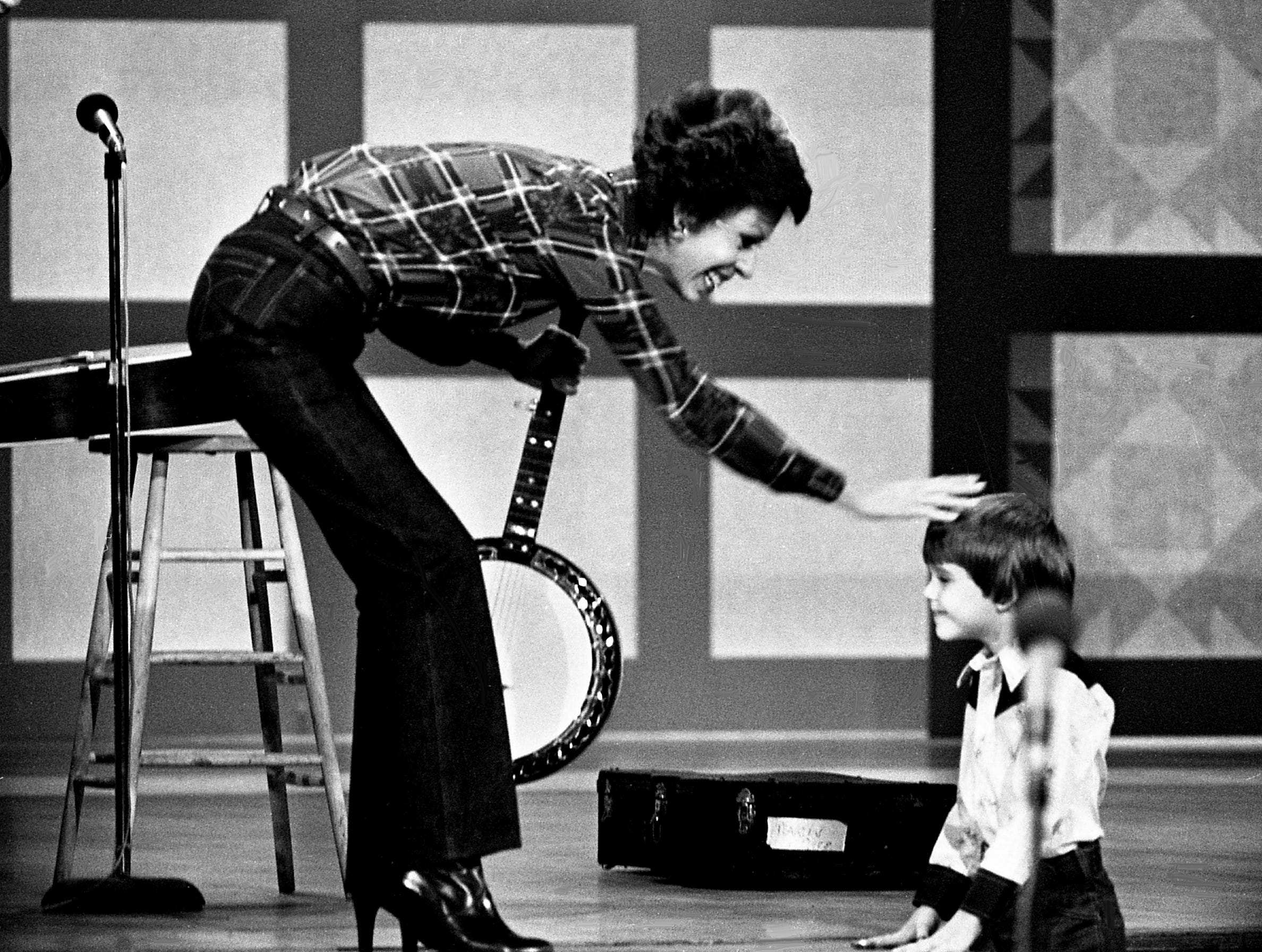 """Six-year-old banjo wizard Lewis Phillips, right, offers to teach Carol Burnett to play the banjo during the """"No one picks like a Nashville picker"""" skit during the taping of the """"Dolly and Carol in Nashville"""" television special before a packed audience at the Grand Ole Opry House Jan. 10, 1979."""