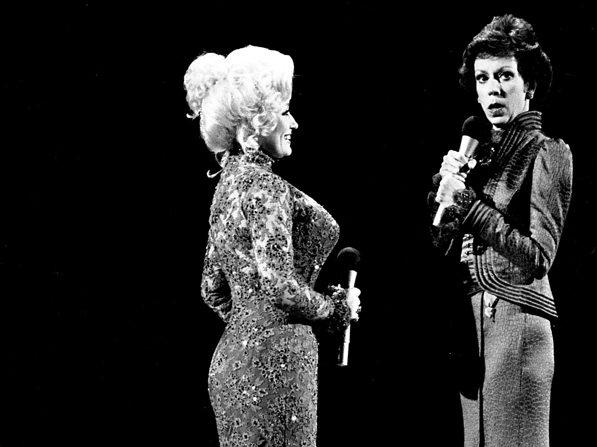 """Dolly Parton and Carol Burnett are performing during their mock-melodramatic love song skit during the taping of the """"Dolly and Carol in Nashville"""" television special before a packed audience at the Grand Ole Opry House Jan. 10, 1979."""