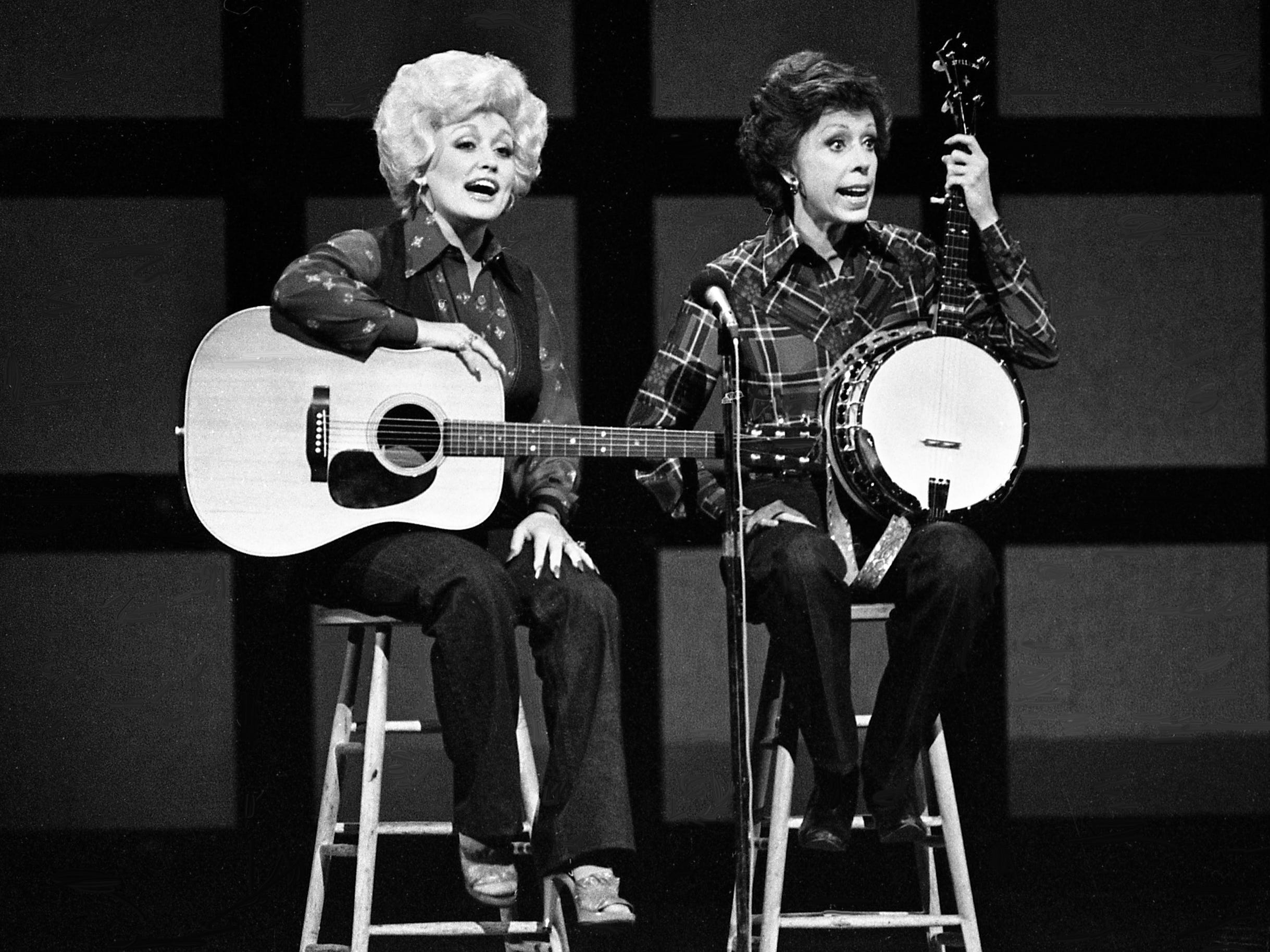 """Dolly Parton, left, asks if there anyone in the audience who can teach Carol Burnett to play the banjo for the """"No one picks like a Nashville picker"""" skit during the taping of the """"Dolly and Carol in Nashville"""" television special before a packed audience at the Grand Ole Opry House Jan. 10, 1979."""
