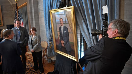Jed DeKalb, a soon-to-be retired state photographer who has worked under five governors takes a photo of Governor Haslam as the governor's portrait was unveiled.