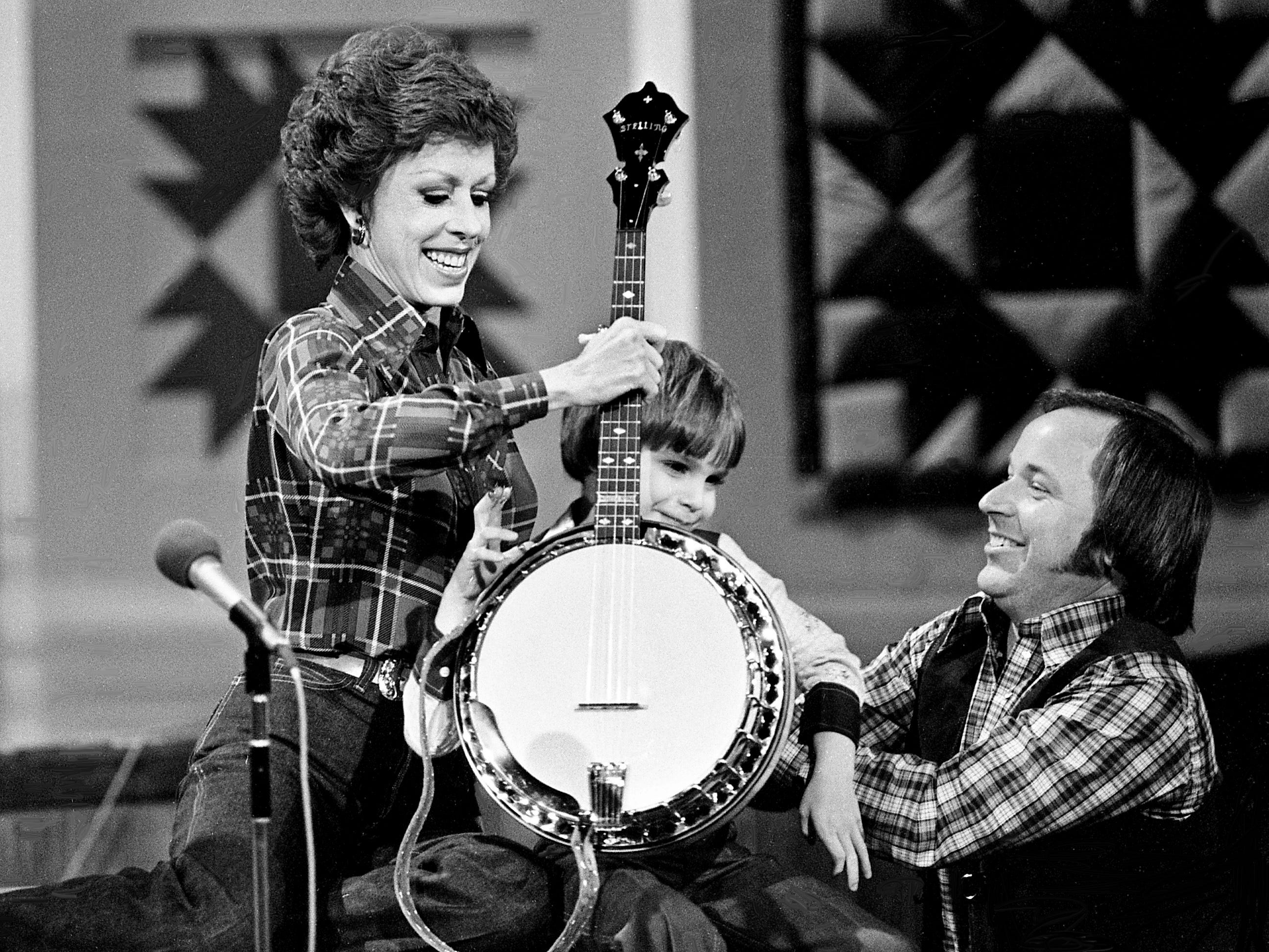 """Six-year-old banjo wizard Lewis Phillips, gets help on the stage to gives Carol Burnett a banjo lesson during the """"No one picks like a Nashville picker"""" skit during the taping of the """"Dolly and Carol in Nashville"""" television special before a packed audience at the Grand Ole Opry House Jan. 10, 1979."""