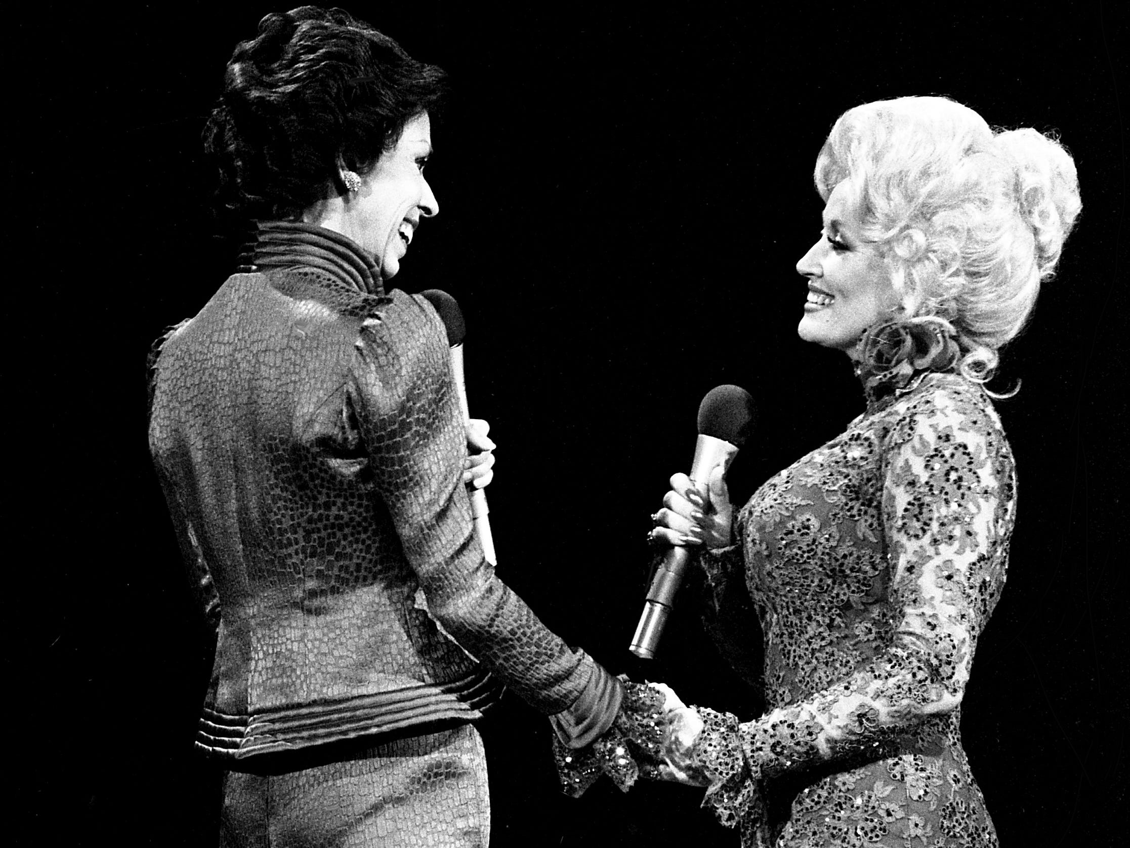 """With the audience on their feet and cheering, Carol Burnett and Dolly Parton share a moment after they finished their mock-melodramatic love song skit during the taping of the """"Dolly and Carol in Nashville"""" television special at the Grand Ole Opry House Jan. 10, 1979."""