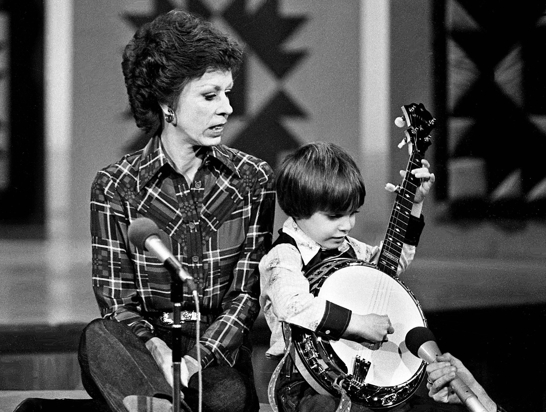 """Six-year-old banjo wizard Lewis Phillips, right, is teaching Carol Burnett how to play the banjo during the """"No one picks like a Nashville picker"""" skit during the taping of the """"Dolly and Carol in Nashville"""" television special before a packed audience at the Grand Ole Opry House Jan. 10, 1979. From the audience, banjo standouts Bashful Brother Oswald and Ramona Jones also gave aid to Burnett."""
