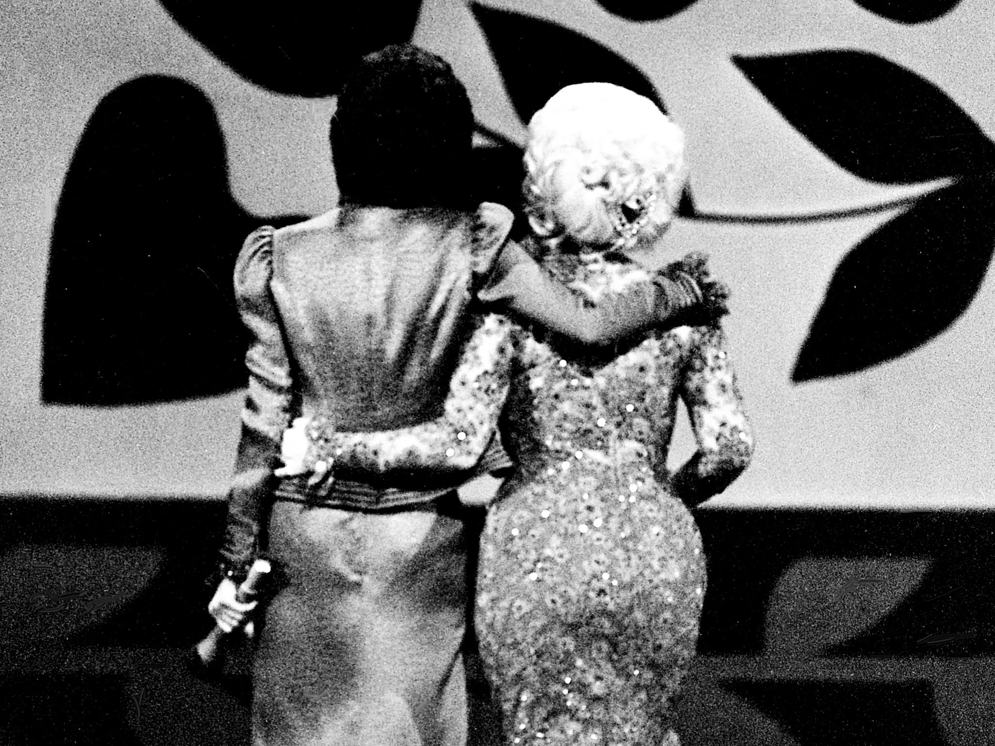 """With the audience on their feet and cheering, Carol Burnett and Dolly Parton walk off the stage after finishing their mock-melodramatic love song skit during the taping of the """"Dolly and Carol in Nashville"""" television special at the Grand Ole Opry House Jan. 10, 1979."""