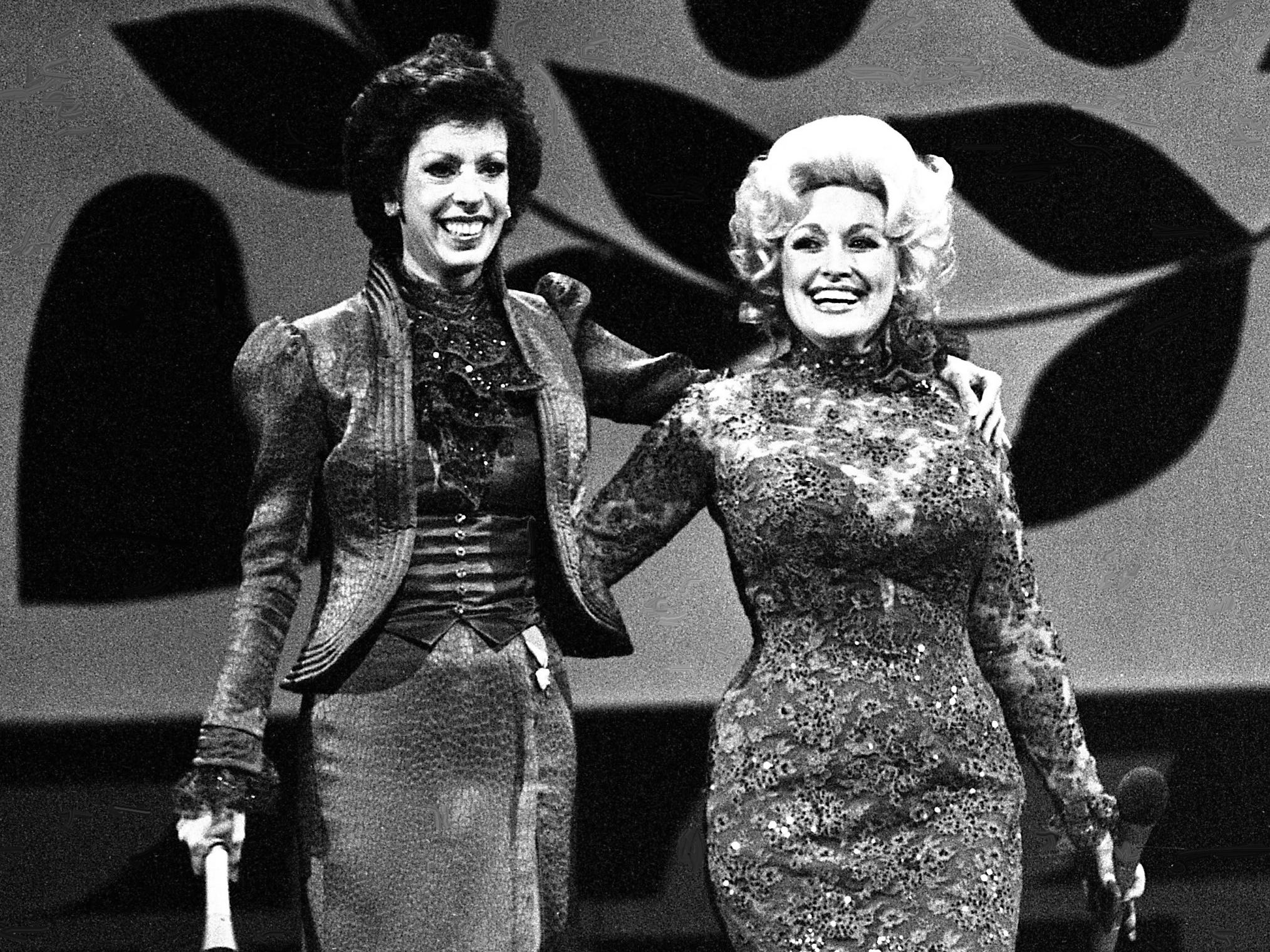 """Carol Burnett and Dolly Parton share a moment as the audience rose and cheered after they finished their mock-melodramatic love song skit during the taping of the """"Dolly and Carol in Nashville"""" television special at the Grand Ole Opry House Jan. 10, 1979."""