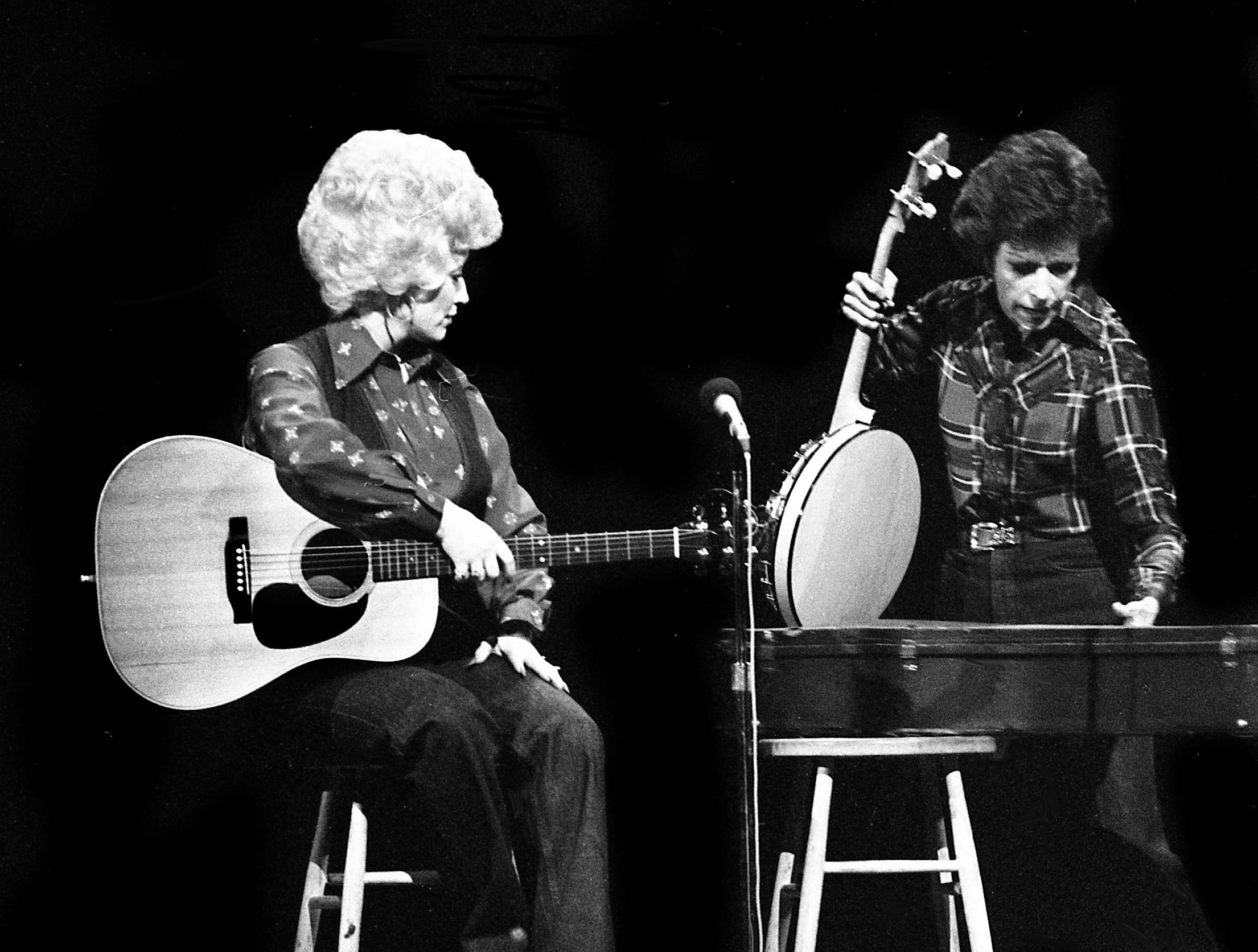 """Dolly Parton, left, looks on as Carol Burnett pull out a banjo for the """"No one picks like a Nashville picker"""" skit during the taping of the """"Dolly and Carol in Nashville"""" television special before a packed audience at the Grand Ole Opry House Jan. 10, 1979. Burnett, who can't play, was determined to make her debut as one."""