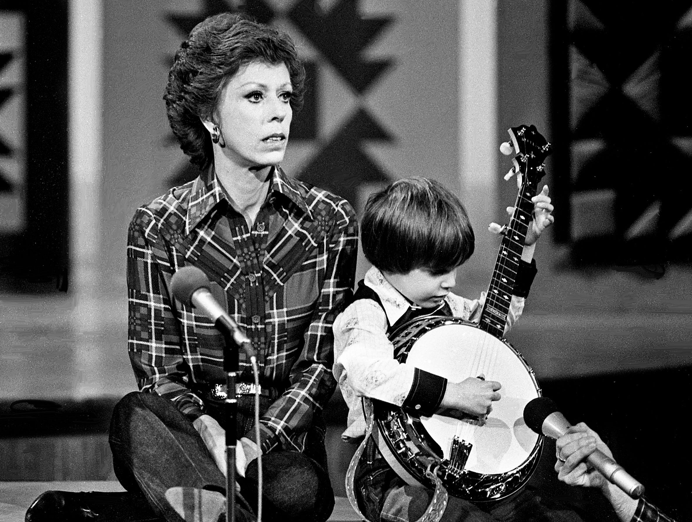 """Six-year-old banjo wizard Lewis Phillips, right, is teaching Carol Burnett how to play the banjo during the """"No one picks like a Nashville picker"""" skit during the taping of the """"Dolly and Carol in Nashville"""" television special before a packed audience at the Grand Ole Opry House Jan. 10, 1979."""