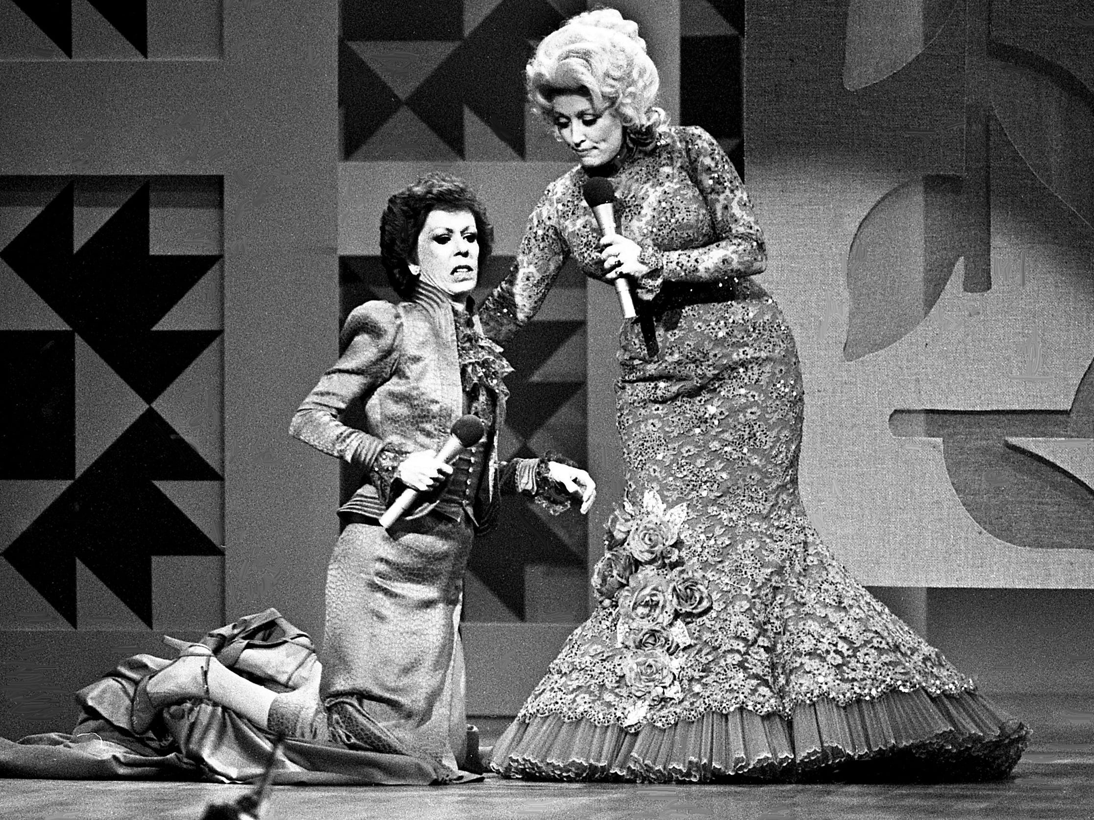 """Dolly Parton, right, helps Carol Burnett after the curtain she was holding gave away and she fell during their mock-melodramatic love song skit during the taping of the """"Dolly and Carol in Nashville"""" television special before a packed audience at the Grand Ole Opry House Jan. 10, 1979."""
