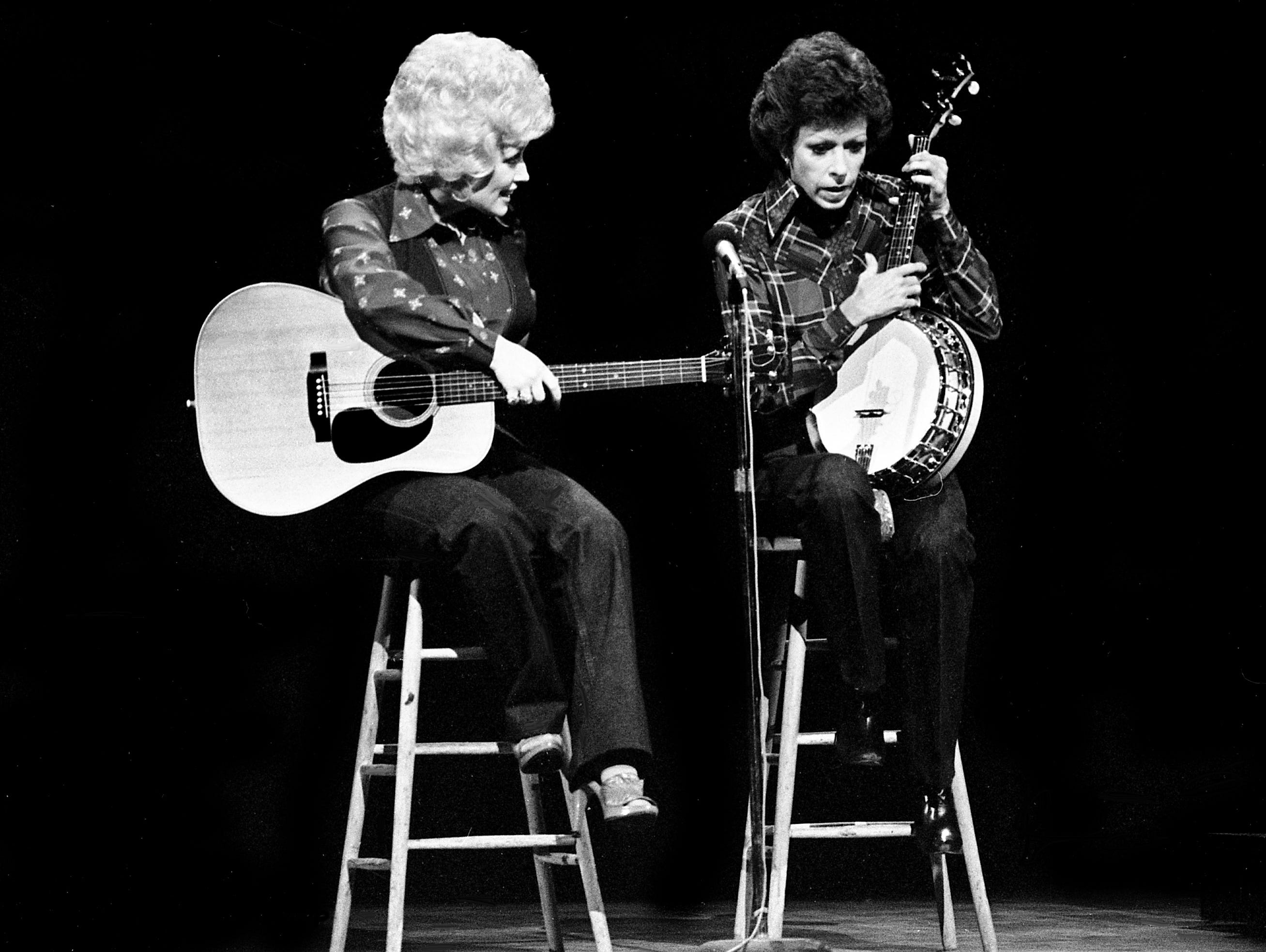 """Dolly Parton, left, looks on as Carol Burnett holds on to the banjo for the """"No one picks like a Nashville picker"""" skit during the taping of the """"Dolly and Carol in Nashville"""" television special before a packed audience at the Grand Ole Opry House Jan. 10, 1979."""