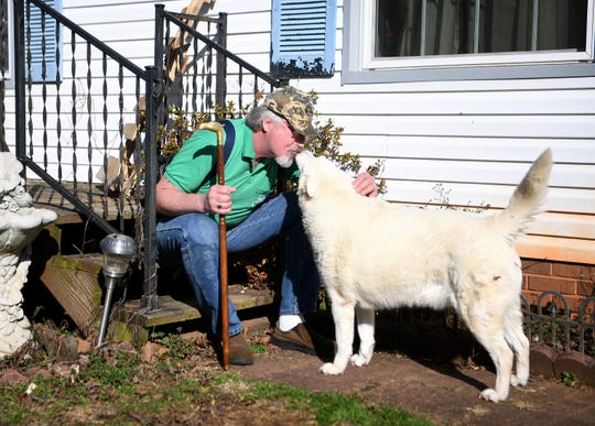 Lenny Quintavalla, 57, pets his dog outside of his home in Maiden, N.C., on Jan. 10, 2019. Quintavalla is a former patient of the PainMD, a pain clinic company that is accused of defrauding the government by giving patients unnecessary injections.