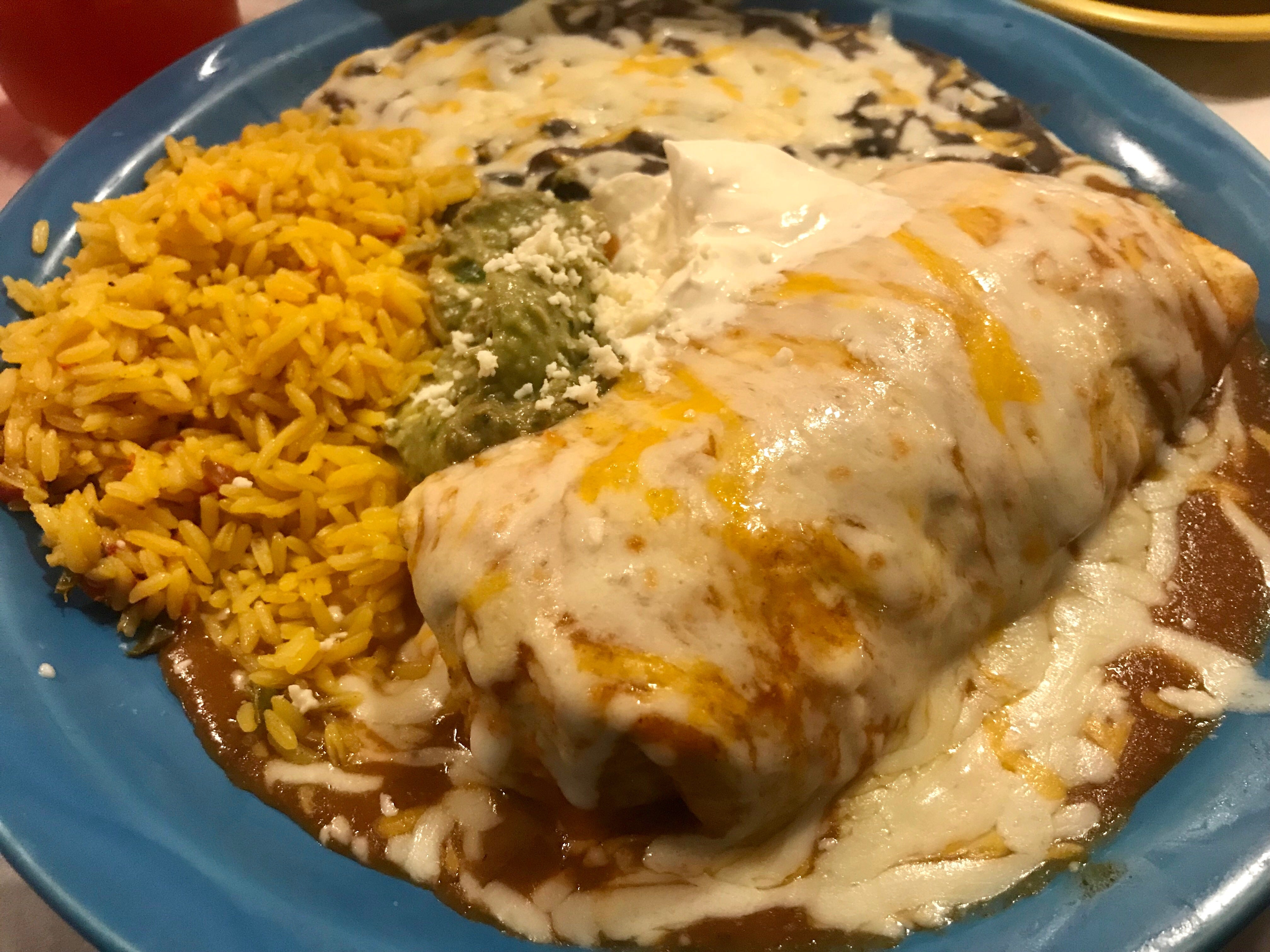 "A burrito La Bamba style, or ""wet,"" which is smothered in salsa ranchero, melted cheese, sour cream and gauc."