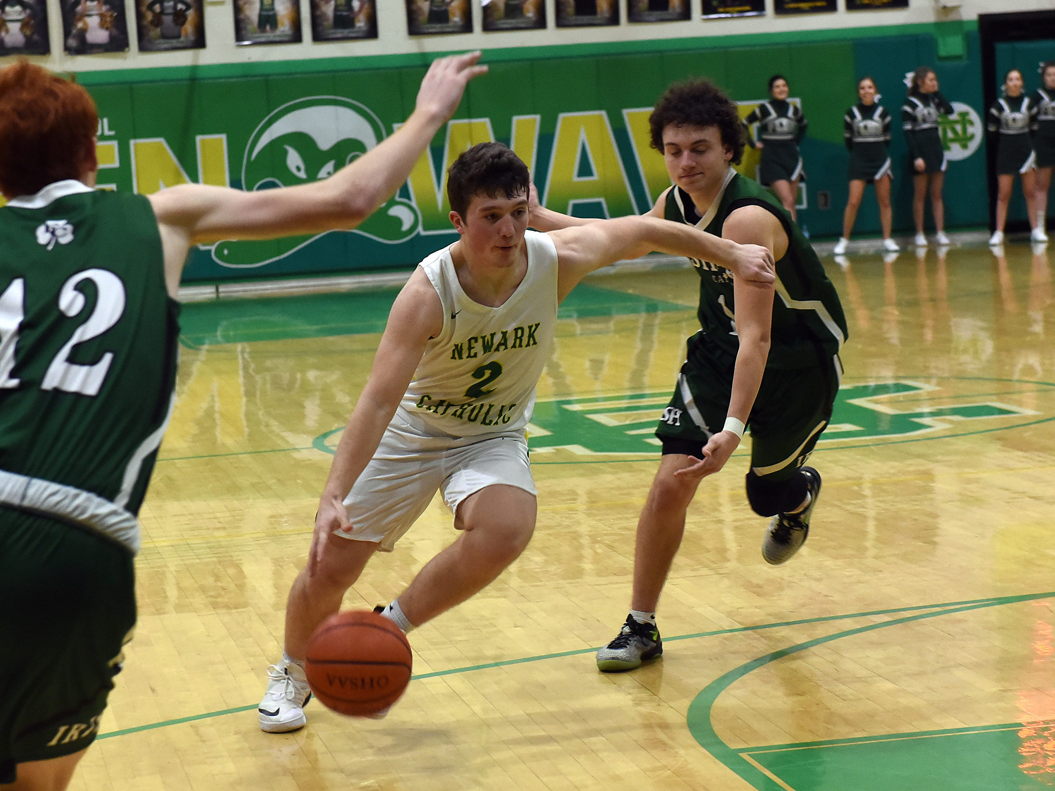 Newark Catholic junior Connor Roesink (center) dodges Fisher Catholic defenders seniors Jayden Boyden (left) and Peyton Shockley (right) during Monday night's game at Newark Catholic. The Irish won with a buzzer-beating 3-pointer defeating the Green Wave 52-49.