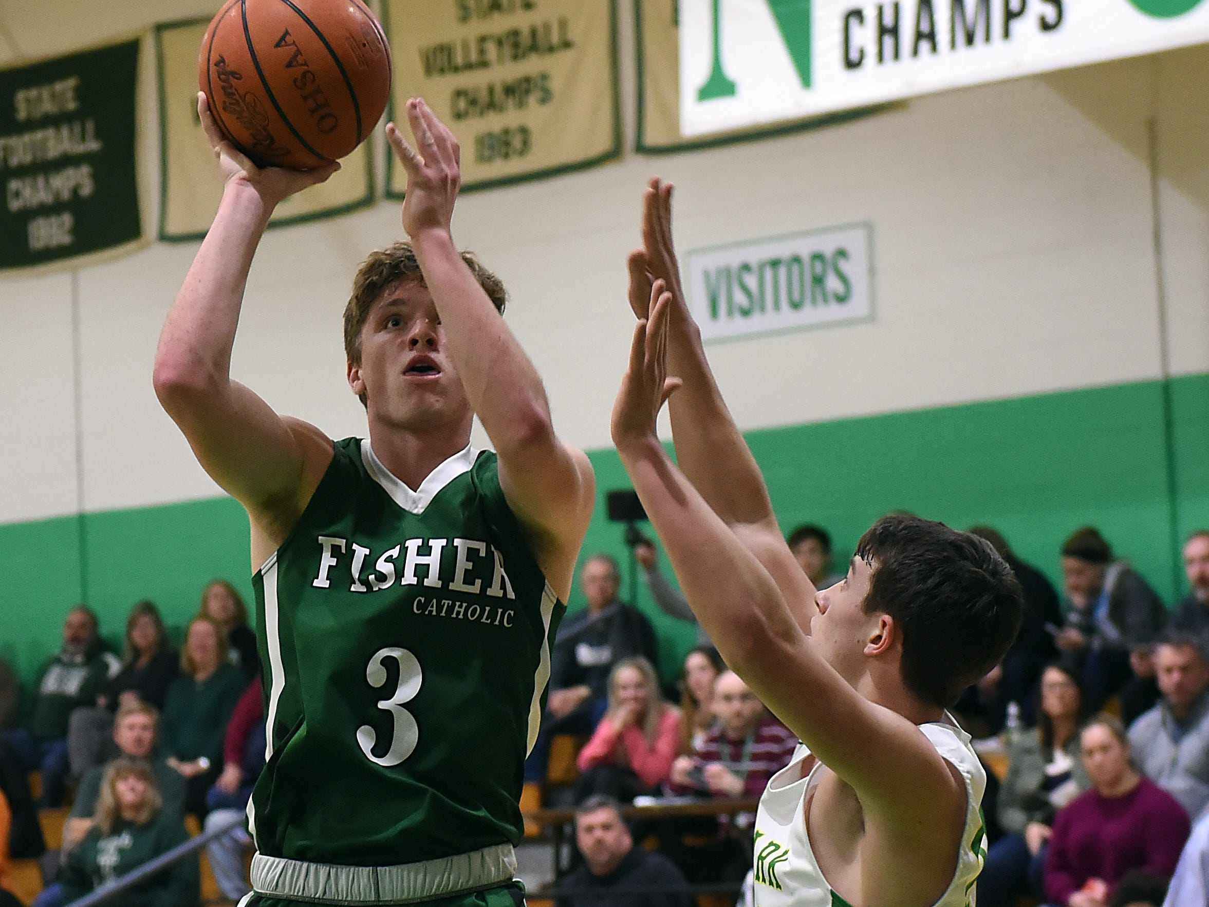 Fisher Catholic senior Collin McCrady shoots against defense from Newark Catholic senior Granger Evans during Monday night's game at Newark Catholic. The Irish won with a buzzer-beating 3-pointer defeating the Green Wave 52-49.