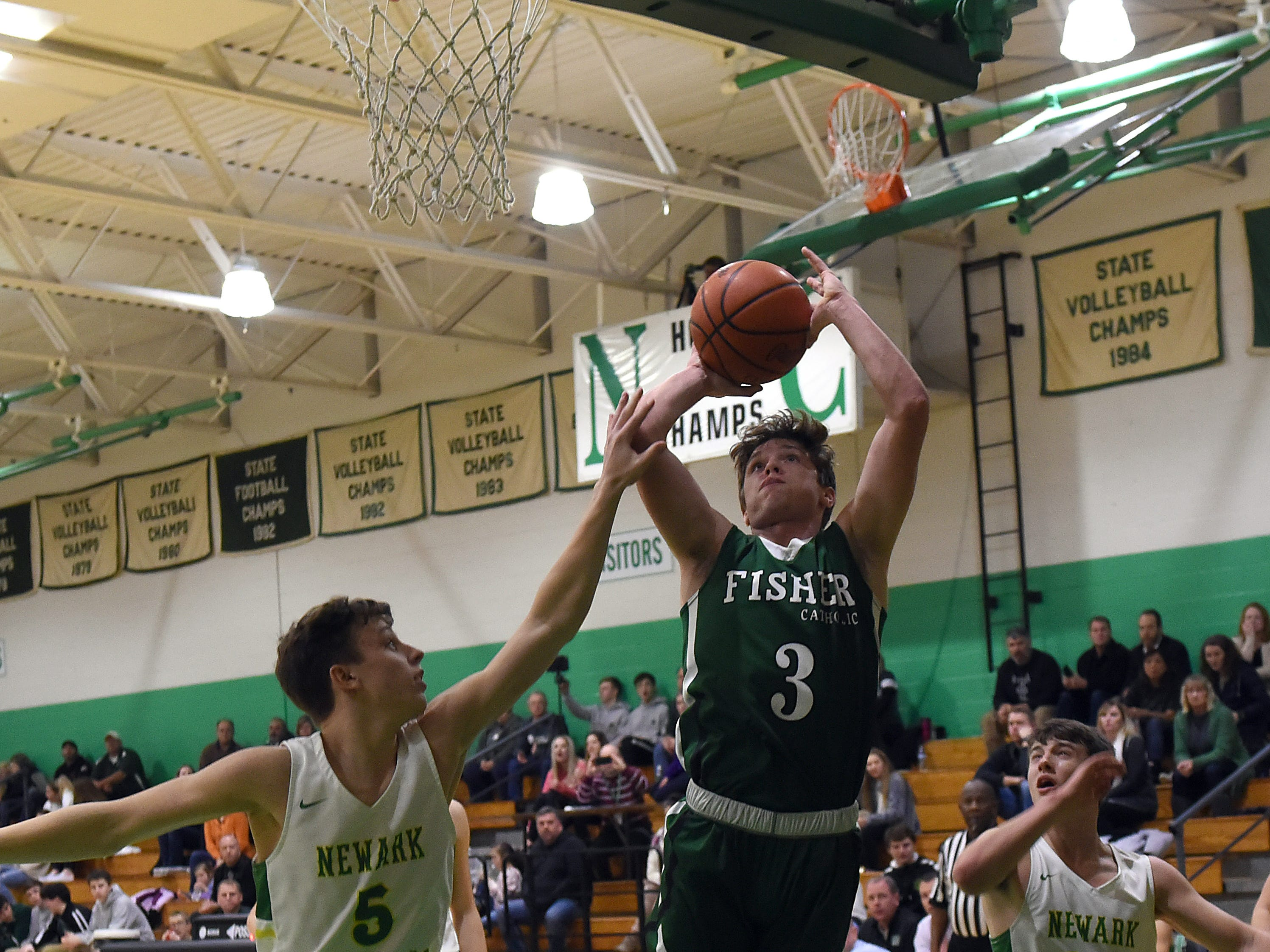 Newark Catholic senior Ian Stacey tries to block a shot from Fisher Catholic senior Collin McCrady during Monday night's game at Newark Catholic. The Irish won with a buzzer-beating 3-pointer defeating the Green Wave 52-49.