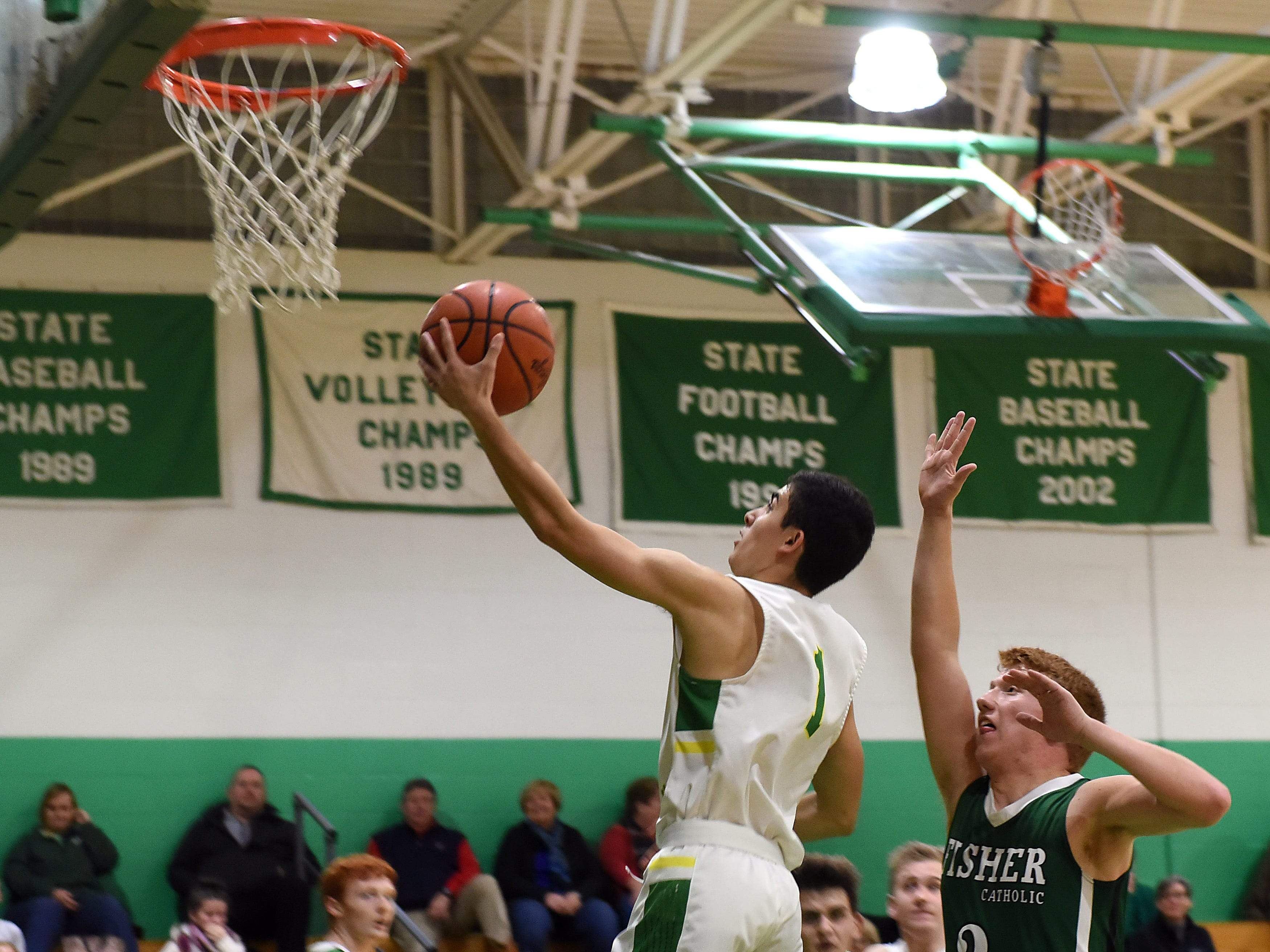 Newark Catholic senior Dow Jones goes up for a layup after breaking past Fisher Catholic senior Carter Brady during Monday night's game at Newark Catholic. The Irish won with a buzzer-beating 3-pointer defeating the Green Wave 52-49.