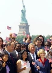 President Bush, center, stands with 29 newly naturalized U.S. citizens for a photo oportunity in front of the Statue of Liberty Tuesday, July 10, 2001, on Ellis Island. Bush attended the ceremony held in the historic Great Hall on Ellis Island and led the new citizens in their first pledge of allegiance.